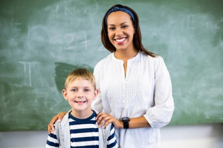 Portrait of smiling teacher and schoolboy standing in classroom at school