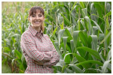 Cheerful female farmer and entrepreneur posing in the corn crop and smiling at camera agriculture and cultivation concept