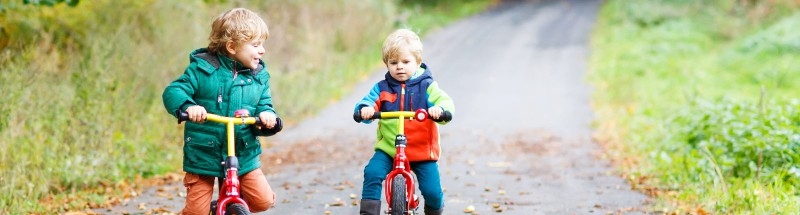Two Little Children Having Fun On Bikes In Autumn Forest.