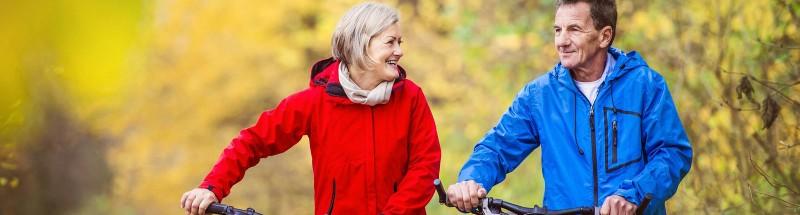 Older couple enjoying walking their bikes