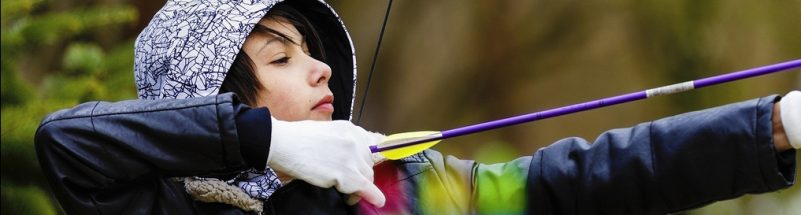 Boy archer shooting with his bow at an outdoor archery range